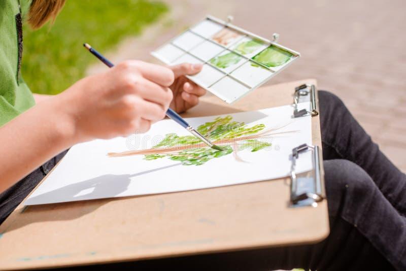 kreativer Künstler malt ein buntes Bild Nahaufnahme von Händen und von Bürste bei Malerei draußen stockbild