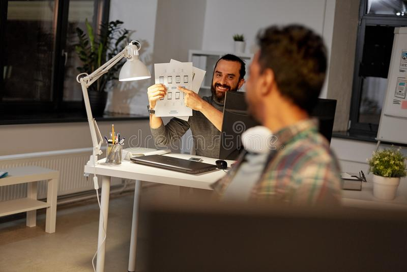 Kreativer Mann, der dem Kollegen Papiere im Büro zeigt stockfotos