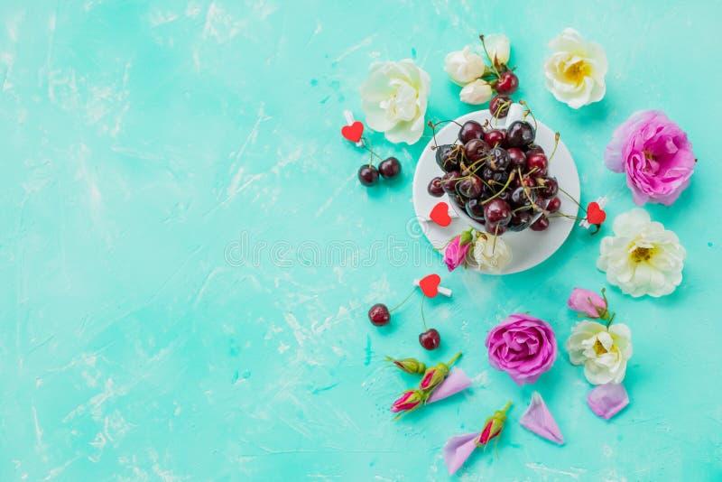 Kreativer Plan gemacht mit blühenden Blumen und Schale mit Beeren auf blauem Hintergrund Flache Lage, Heiratshintergrund lizenzfreie stockfotos