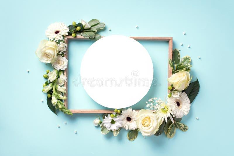 Kreativer Plan mit weißen Blumen, Papierkreis für copyspace über blauem Hintergrund Draufsicht, flache Lage Fr?hling und lizenzfreies stockfoto