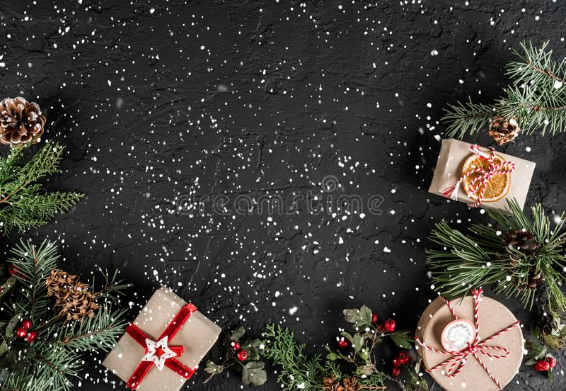 Kreativer Planrahmen gemacht von den Weihnachtsbaumasten, Geschenke, Beeren, Kiefernkegel auf dunklem Hintergrund mit Schneeflock stockfoto