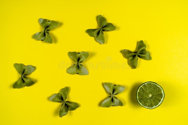 Kreativer Sommerplan gemacht vom Kalk und von farbigem Teigwarengrieß papillon auf hellem gelbem Hintergrund Minimales Konzept de stockfotografie
