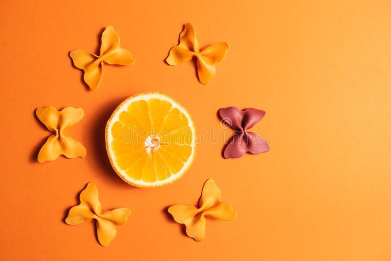 Kreativer Sommerplan gemacht von den Orangen und von farbigem Teigwarengrieß papillon auf Leuchtorangehintergrund Minimales Konze stockbild