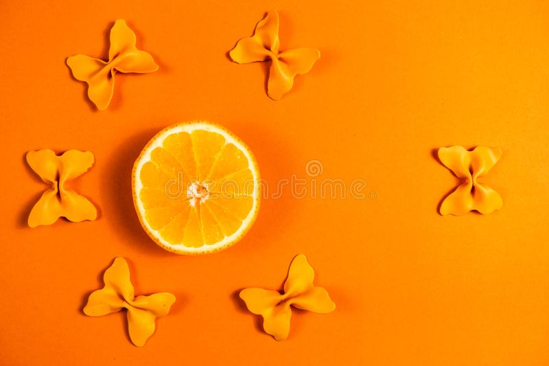 Kreativer Sommerplan gemacht von den Orangen und von farbigem Teigwarengrieß papillon auf Leuchtorangehintergrund Minimales Konze lizenzfreie stockbilder