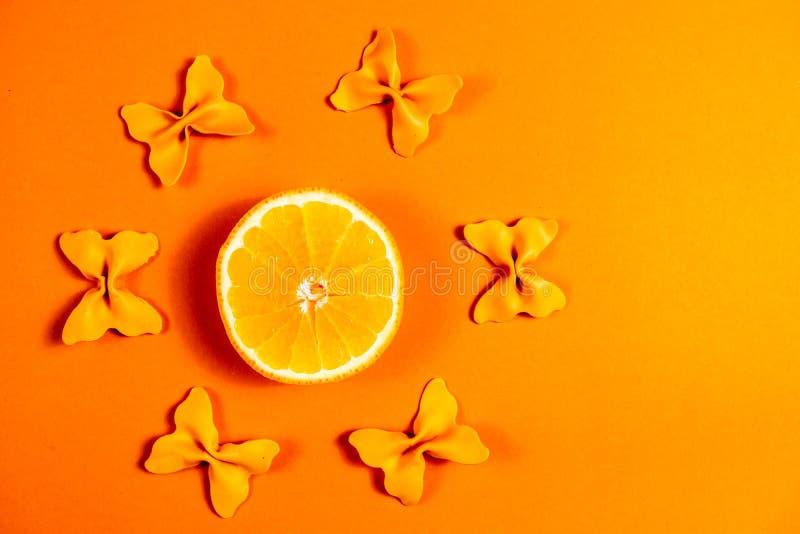 Kreativer Sommerplan gemacht von den Orangen und von farbigem Teigwarengrieß papillon auf Leuchtorangehintergrund Minimales Konze stockbilder