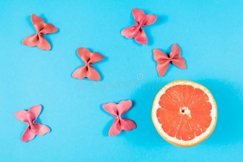 Kreativer Sommerplan gemacht von der Pampelmuse und von farbigem Teigwarengrieß papillon auf hellem blauem Hintergrund Minimales  lizenzfreie stockbilder