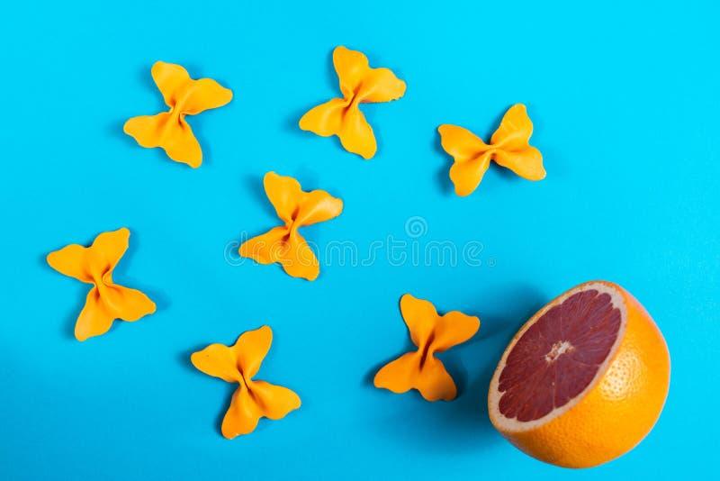 Kreativer Sommerplan gemacht von der Pampelmuse und von farbigem Teigwarengrieß papillon auf hellem blauem Hintergrund Minimales  lizenzfreies stockbild