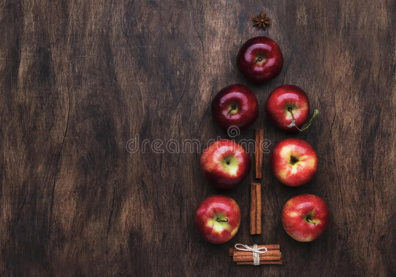 Kreativer Weihnachtsbaum aus roten Äpfeln, Zimt- und Anisstern auf braunem Holzboden lizenzfreie stockfotos