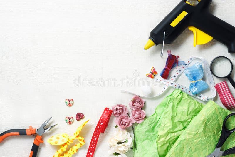 Kreatives Arbeitsplatzkonzept: Draufsicht der Tabelle mit Elementen für scrapbookin und Werkzeugen für Dekoration lizenzfreie stockfotos