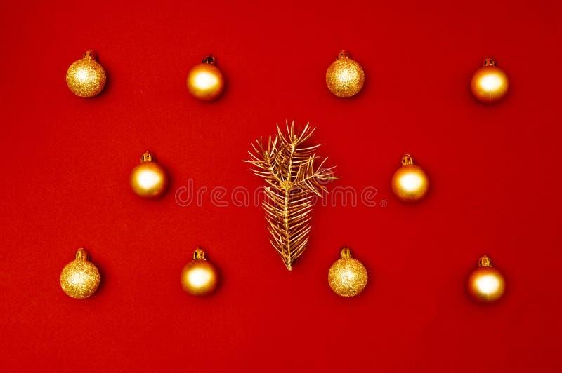 Kreatives Dekorationsmuster des mehrfachen Weihnachtsgoldflitters mit goldener Kieferniederlassung auf dem roten Hintergrund lizenzfreie stockfotos