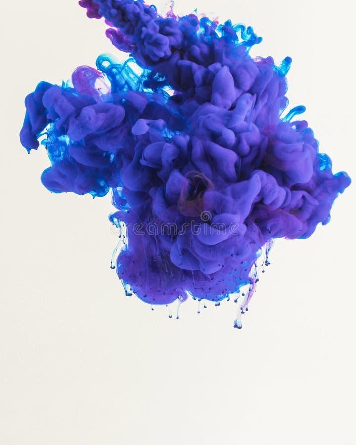 kreatives Design mit fließen blaue und purpurrote rauchige Tinte, lokalisiert auf Weiß lizenzfreie stockfotos