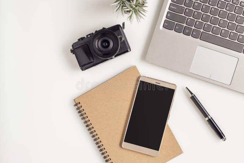 Kreatives flaches gelegtes Foto des Arbeitsplatzschreibtisches mit Laptop, leerem Kopienraum Smartphone und Kamera auf weißem Tab stockfoto
