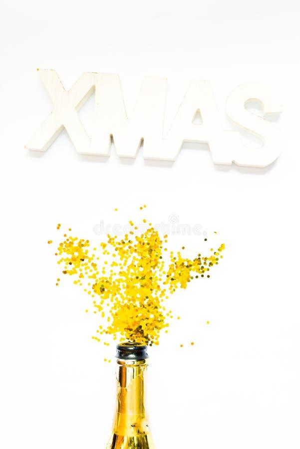 Kreatives Foto von Champagnerflasche mit Konfetti auf weißem Hintergrund mit einer riesigen Weihnachtsdekoration auf der Decke, W stockbild