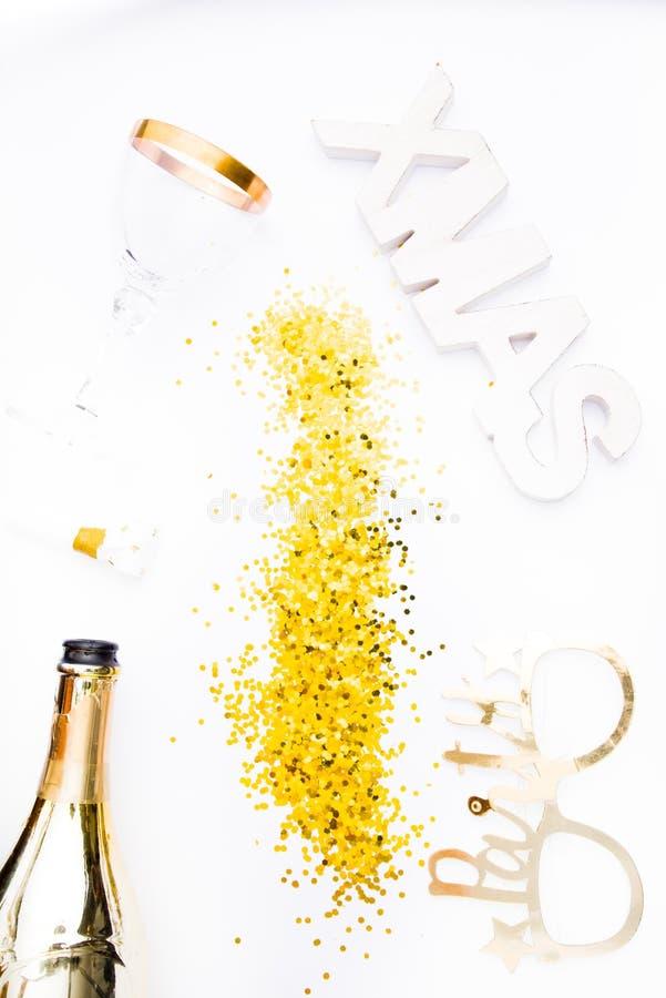 Kreatives Foto von Champagnerflasche mit Konfetti auf weißem Hintergrund mit einer riesigen Weihnachtsdekoration auf der Decke, W lizenzfreie stockfotografie