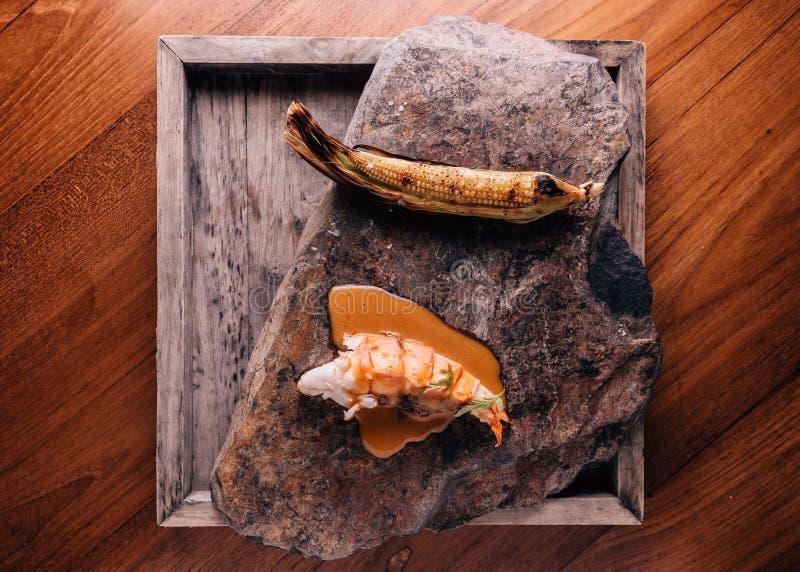 Kreatives Geldstrafen-Speisen: Gegrillter Hummer, der mit gelber Curry- und Kokosnussstausoße mit gegrilltem Mais gießt lizenzfreie stockbilder
