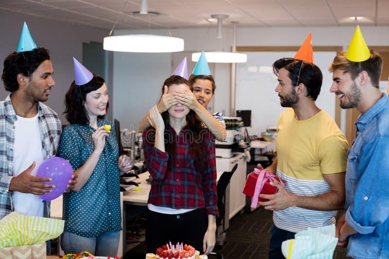 Kreatives Geschäftsteam, das eine Überraschung zu ihrem College auf ihrem Geburtstag gibt lizenzfreies stockfoto