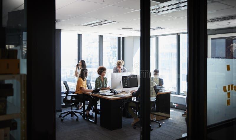 Kreatives Geschäftsteam, das in einem zufälligen Büro, gesehene durch Glaswand zusammenarbeitet stockbilder