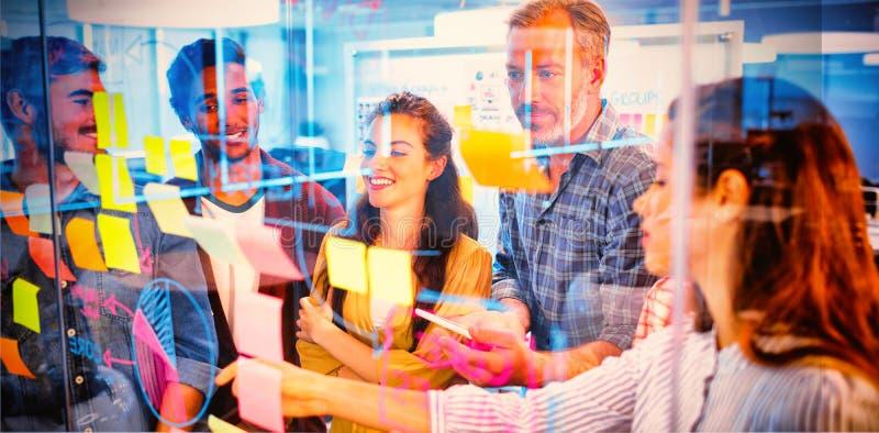 Kreatives Geschäftsteam, das klebrige Anmerkungen über Glasfenster betrachtet lizenzfreie stockfotos