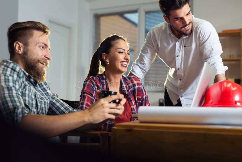 Kreatives Geschäftsteam, das schwer zusammen im zufälligen Büro arbeitet stockbild