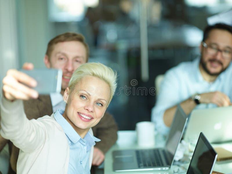 Kreatives Geschäftsteam, das Selfie bei der Sitzung nimmt lizenzfreie stockfotografie