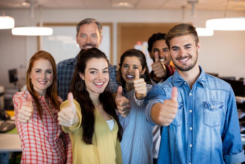 Kreatives Geschäftsteam, das sich Daumen im Büro zeigt stockfoto