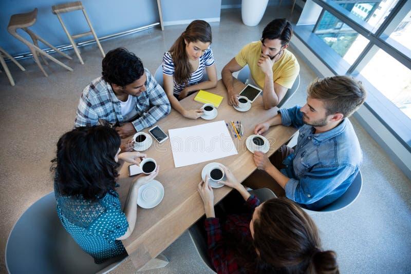 Kreatives Geschäftsteam, welches das Treffen über Kaffee im Konferenzzimmer hat stockbilder