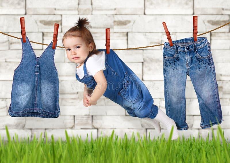 Kreatives Konzept der ausfallen Hausarbeit, das lustige Kind, das an hängt, kleiden stockfotografie