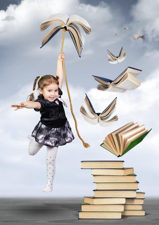 Kreatives Konzept der Bildung, Kindermädchenfliege auf Buch lizenzfreies stockbild