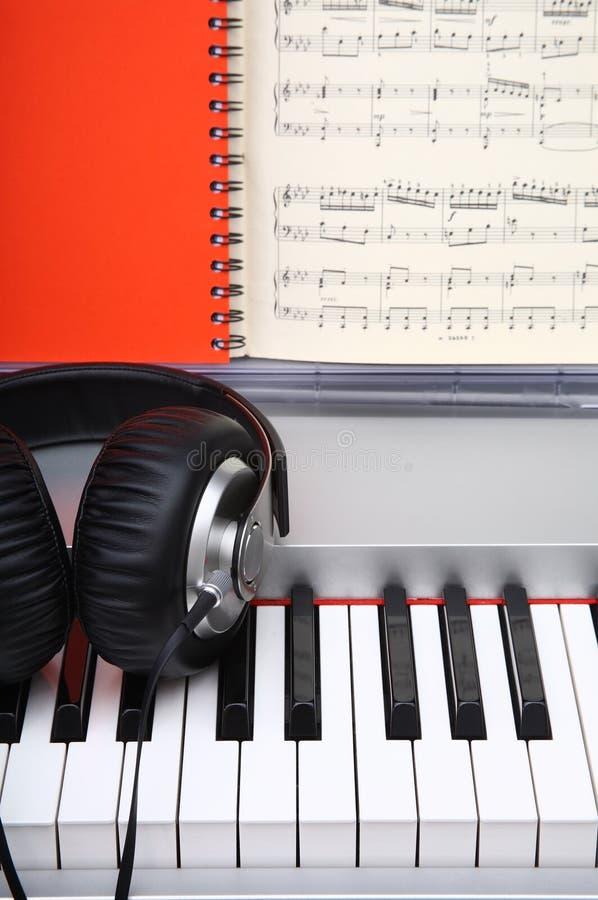 Kreatives Konzept von Schlüsseln eines Digitalpianos mit großen schwarzen ledernen Kopfhörern lizenzfreies stockbild