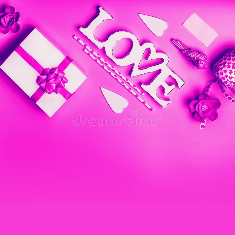 Kreatives Liebeshintergrundkonzept in der Rosapurpurroten Neonfarbe Wort-Liebeszeichen mit Geschenkbox und Dekorationen Valentins stockfotografie
