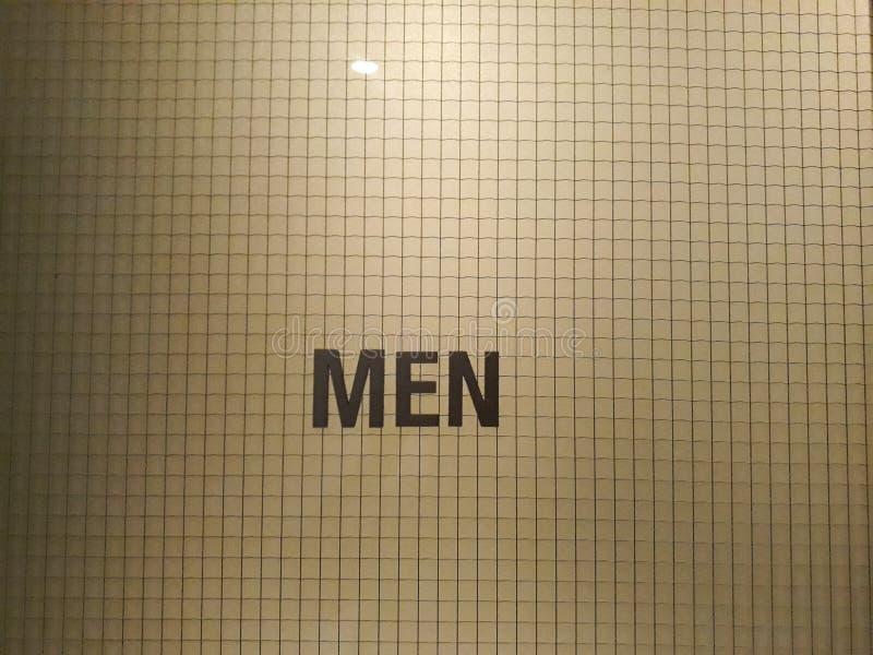 Kreatives Manntoilettenzeichen mit Wort bedeutet Toilette auf abstrakter Wand lizenzfreie stockbilder