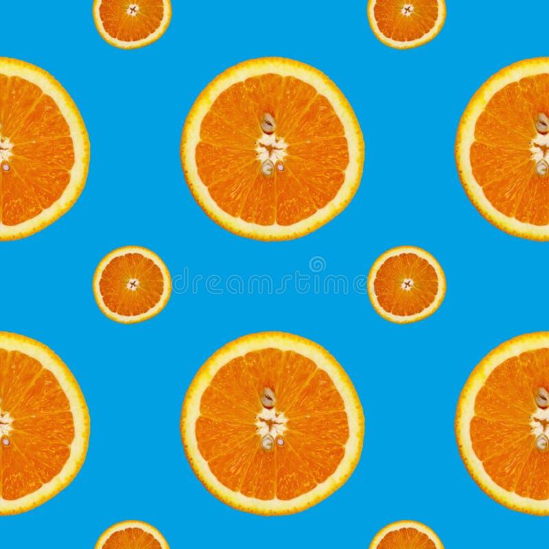 Kreatives Muster gemacht von der Orange auf blauem Hintergrund Chef gießt Olivenöl über frischem Salat in der Gaststätteküche stockfotos