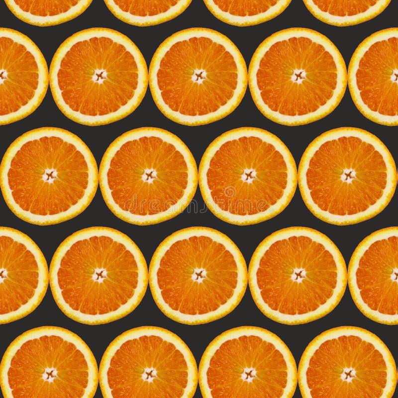 Kreatives Muster gemacht von der Orange auf schwarzem Hintergrund Chef gießt Olivenöl über frischem Salat in der Gaststätteküche stockbilder