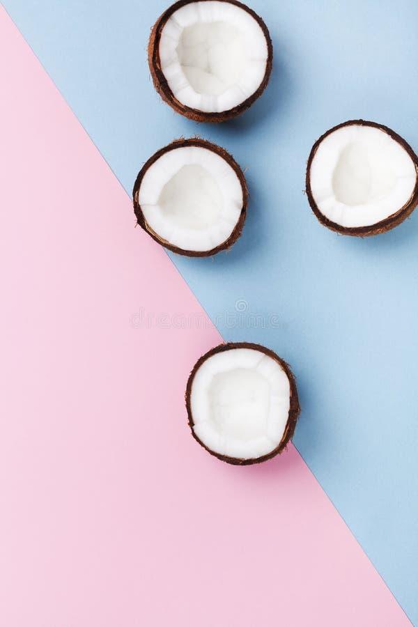 Kreatives Sommermuster für modernes Design Kokosnussfrucht halb auf Draufsicht des minimalen Pastellhintergrundes Flache Lage stockfotos