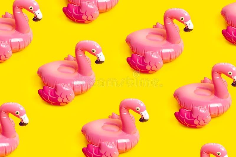 Kreatives Sommerstrandkonzept Muster vom aufblasbaren rosa Miniflamingo auf gelbem Hintergrund, Poolflosspartei Flache Lage, Kopi lizenzfreie stockfotos