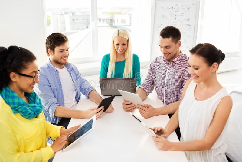 Kreatives Team mit Tabellencomputern im Büro lizenzfreie stockfotografie