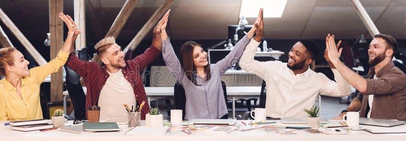 Kreatives Team schließen sich den Händen an, die sich zusammen im modernen Büro treffen stockbilder