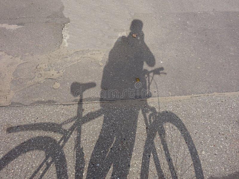 Kreatives Zyklus-Fahrrad-Radfahrer-Schatten-Schattenbild auf Asphalt Road stockbilder