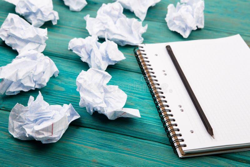 Kreativitetbegrepp - notepad, blyertspenna och skrynkligt papper på blått arkivbild