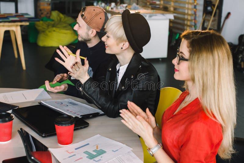 Kreatywnie agencyjny spotkanie - grupa ludzie biznesu opowiada podczas konferencji przy biurem i oklaskiwać w przypadkowej odzież obraz royalty free