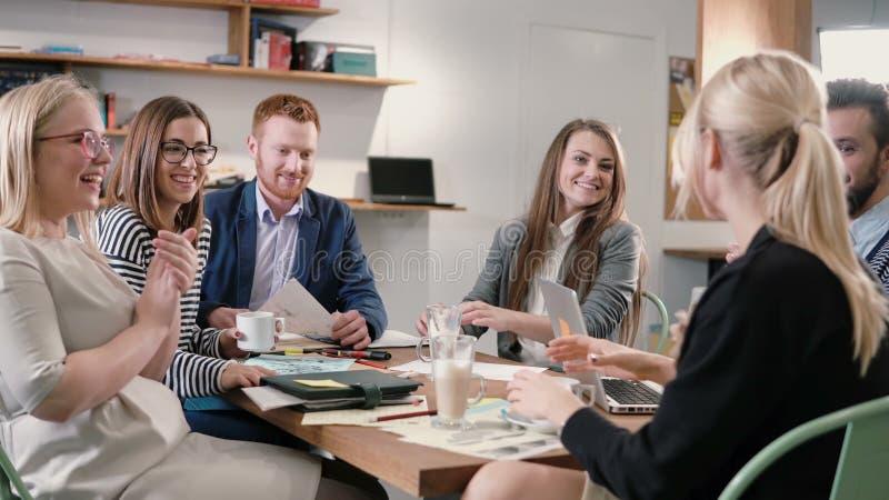 Kreatywnie biznes drużyna przy stołem w nowożytnym początkowym biurze żeński mówca oferuje doskonałego pomysł i drużyna wspiera o zdjęcie stock