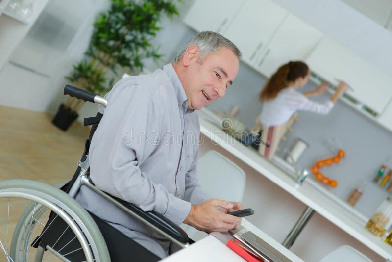 Kreatywnie biznesmen w wózku inwalidzkim na telefonie w domu fotografia royalty free