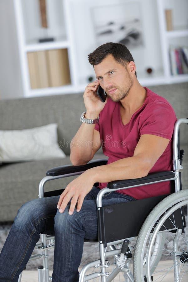 Kreatywnie biznesmen w wózku inwalidzkim na telefonie przy biurem obraz stock