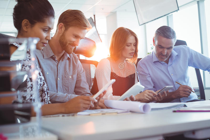 Kreatywnie biznesowi koledzy używa cyfrowe pastylki przy biurem obraz royalty free
