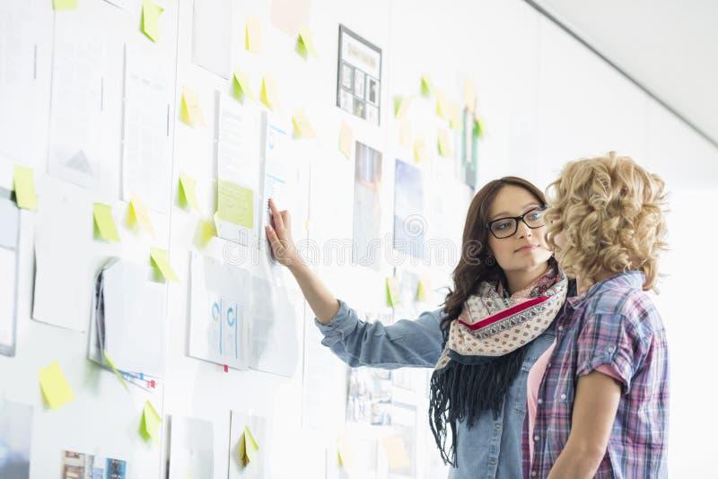 Kreatywnie bizneswomany dyskutuje nad papierami wtykali na ścianie w biurze zdjęcie stock