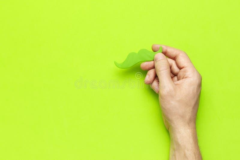 Kreatywnie dekoracji pojęcia mężczyzn ręk chwyta zieleni partyjny wąsy, wsparcia dla fotografii booths, karnawał bawi się na ziel obraz royalty free