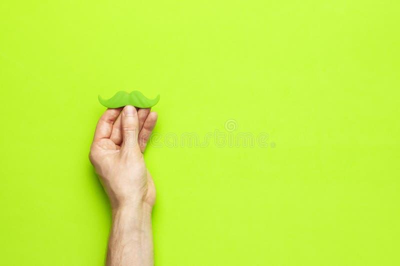 Kreatywnie dekoracji pojęcia mężczyzn ręk chwyta zieleni partyjny wąsy, wsparcia dla fotografii booths, karnawał bawi się na ziel zdjęcie stock