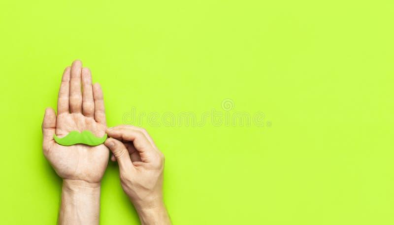 Kreatywnie dekoracji pojęcia mężczyzn ręk chwyta zieleni partyjny wąsy, wsparcia dla fotografii booths, karnawał bawi się na ziel obrazy stock