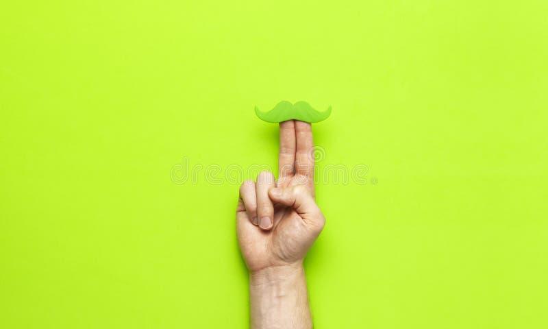 Kreatywnie dekoracji pojęcia mężczyzn ręk chwyta zieleni partyjny wąsy, wsparcia dla fotografii booths, karnawał bawi się na ziel fotografia royalty free