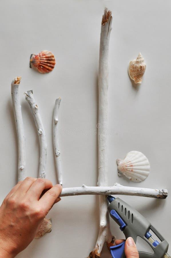 Kreatywnie drewniana kij choinka dekorował z rozgwiazdą i seashell Mistrzowski klasy i procesu produkcyjnego kleidła pistolet Ove fotografia stock